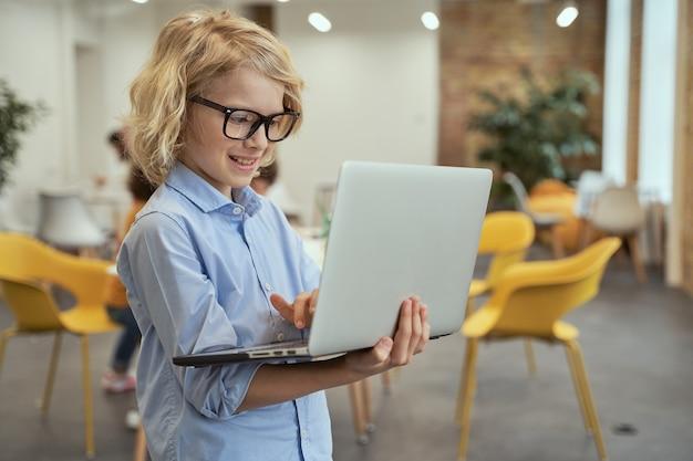 Ritratto di un ragazzino carino con gli occhiali che sorride mentre tiene e usa il laptop in piedi in a