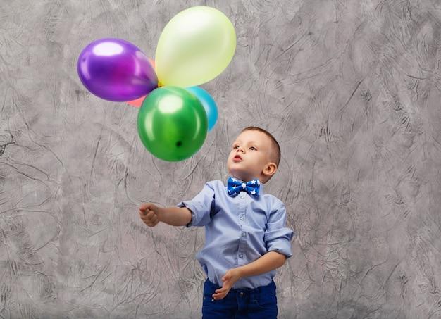 Ritratto di un ragazzino sveglio che tiene palloncini