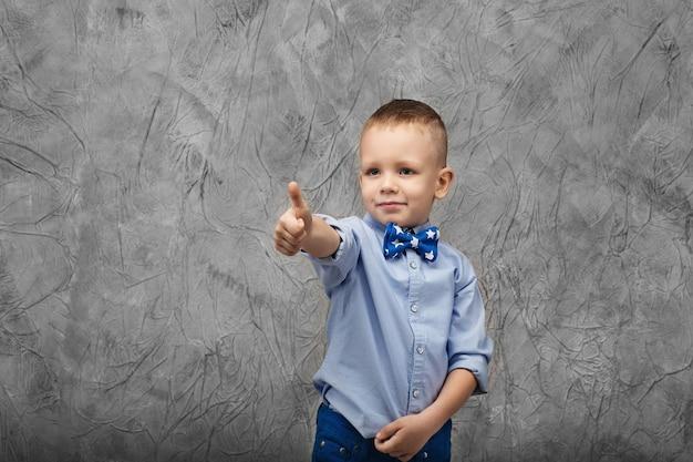 Ritratto di un ragazzino sveglio in jeans, camicia blu e farfallino su un tessuto grigio in studio