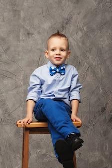 Ritratto di un ragazzino sveglio in jeans, camicia blu e farfallino