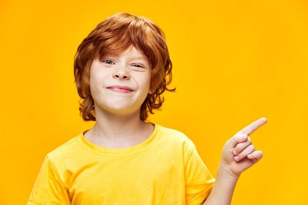 Ritratto di un ragazzino sveglio con gesti dai capelli rossi con le mani in una maglietta gialla