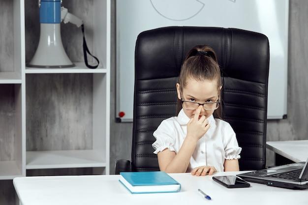 Ritratto di un bambino carino raffigurante il capo dell'agenzia a un tavolo bianco