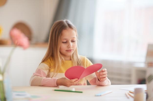 Ritratto di bambina sveglia che tiene carta a forma di cuore e sorridente mentre è seduto al tavolo in interni domestici accoglienti, spazio di copia