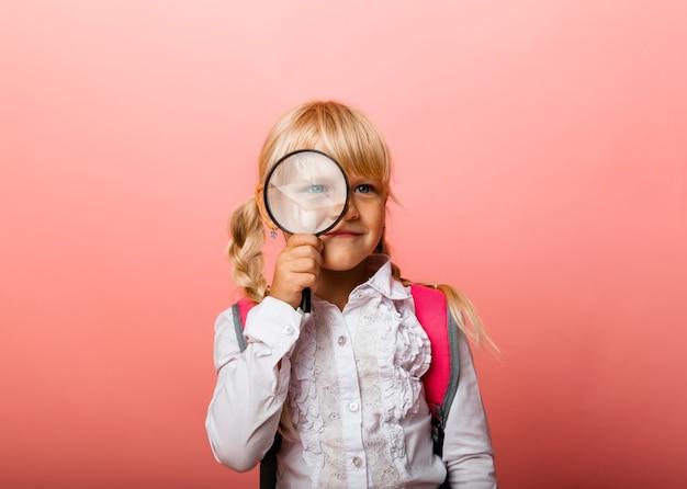Ritratto di una bambina carina che tiene una lente d'ingrandimento vicino al suo occhio su uno sfondo rosa.