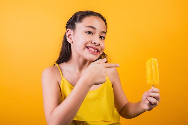 Ritratto di una bambina carina che tiene un ghiacciolo giallo su sfondo giallo.