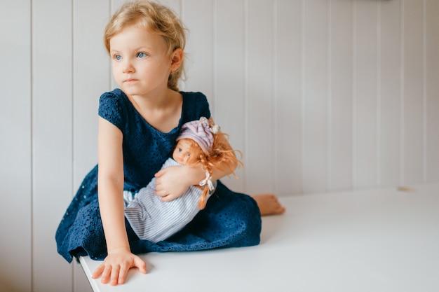Il ritratto della bambina sveglia tiene la sua bella barbie, si siede nella stanza del bambino luminosa, guarda da parte