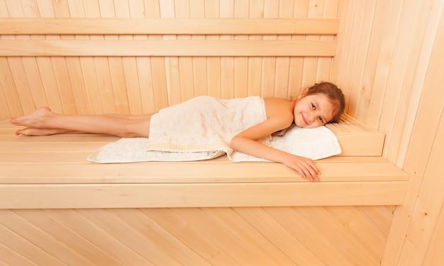 Ritratto di una bambina carina che si rilassa sulla panchina della sauna