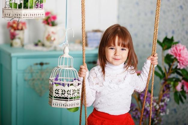Ritratto di una bambina carina cavalca su un'altalena all'interno con decorazioni shabby chic