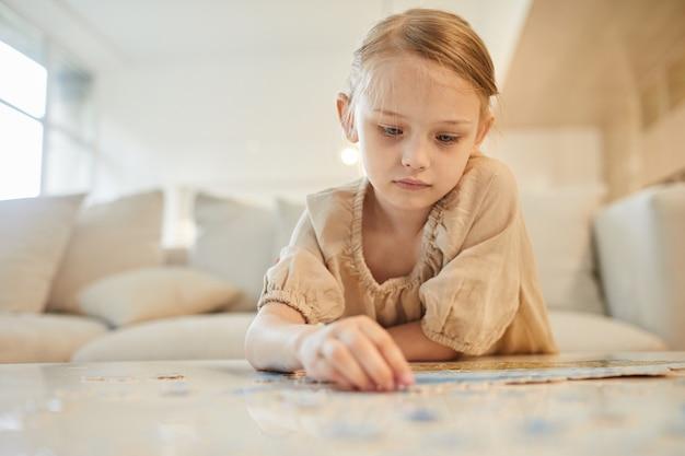 Ritratto di ragazza carina risolvere puzzle da solo mentre è seduto sul divano in interni domestici