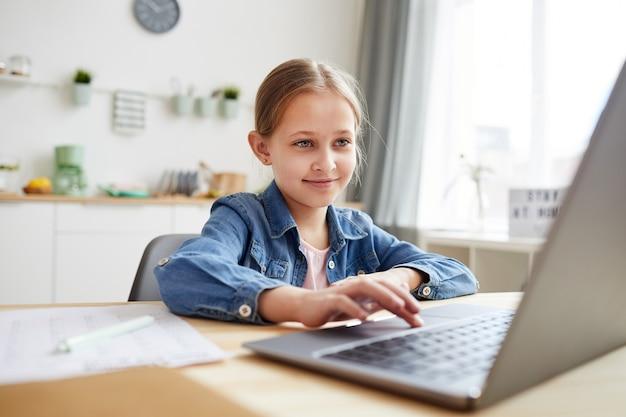 Ritratto di ragazza carina utilizzando laptop e sorridente mentre studia online a casa in interni accoglienti, copia dello spazio