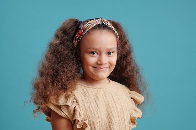 Ritratto di una bambina carina con una bella acconciatura che guarda l'obbiettivo isolato su sfondo blu