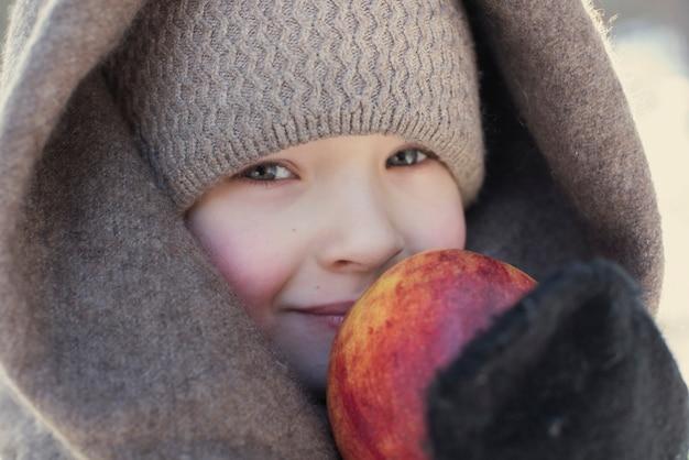 Un ritratto di una bambina carina con lo scialle nel parco invernale