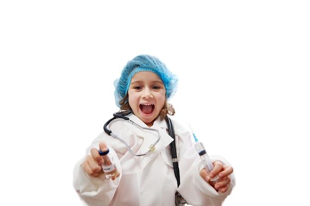 Ritratto di una bambina sveglia con lo stetoscopio in uniforme medica che tiene la fiala e la siringa del vaccino