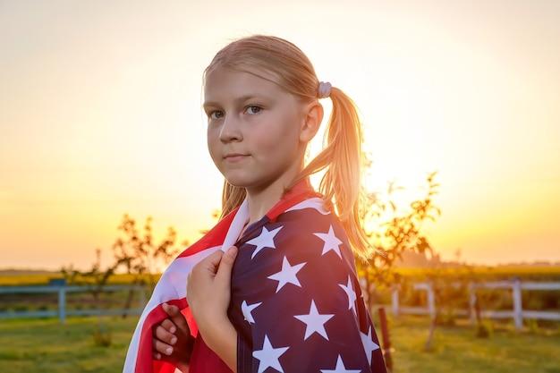 Ritratto di una bambina carina avvolta in una bandiera americana in piedi in un campo