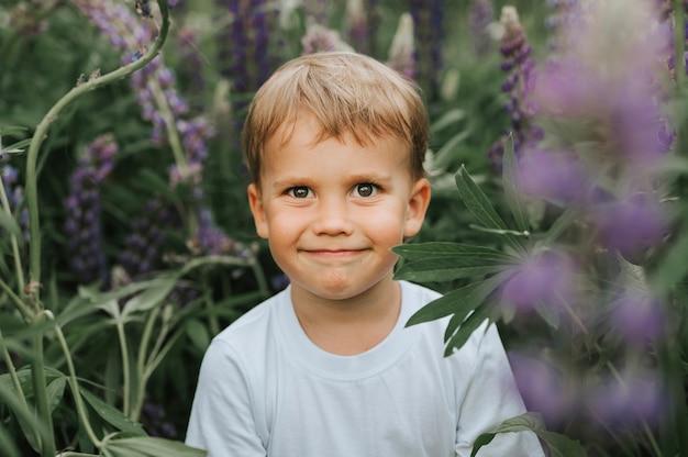 Ritratto di un ragazzino felice sveglio con i lupini della fioritura