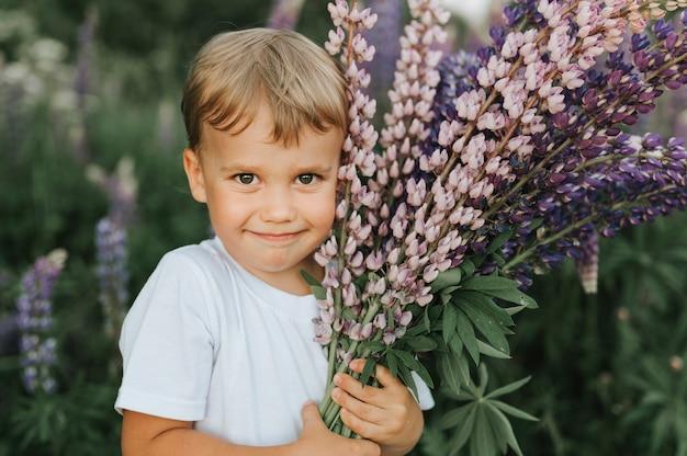 Ritratto di un ragazzino felice carino con bouquet di lupini fioriti