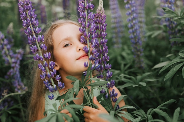 Ritratto di una piccola ragazza felice sveglia che gode dei lupini della fioritura