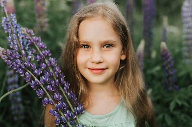 Ritratto di una piccola ragazza felice sveglia con i lupini della fioritura