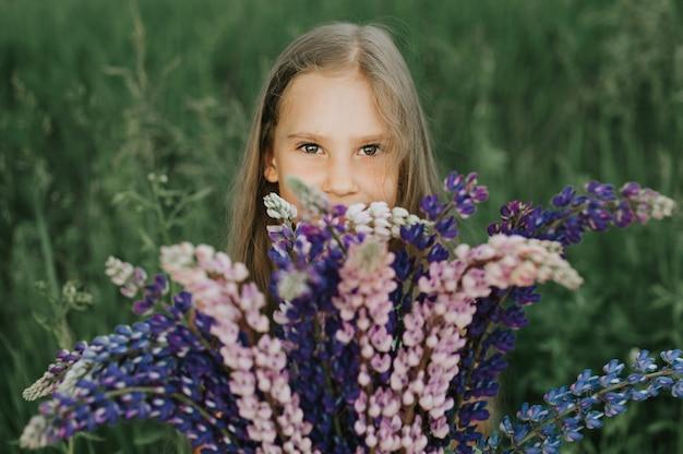 Ritratto di una ragazza felice poco carina con bouquet di lupini fioriti