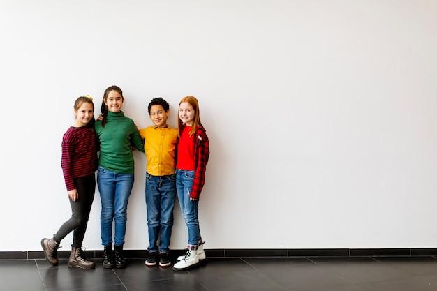 Ritratto di simpatici ragazzini in jeans che guarda l'obbiettivo e sorridente, in piedi contro il muro bianco