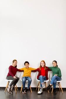 Ritratto di simpatici ragazzini in jeans seduti su sedie contro il muro bianco