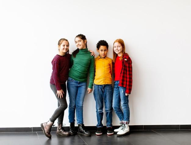 Ritratto di simpatici ragazzini in jeans sorridente, in piedi contro il muro bianco