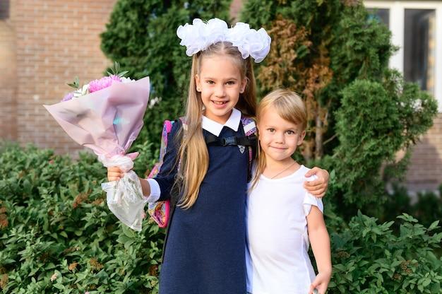 Ritratto di una graziosa bambina di prima elementare di sette anni con un mazzo di fiori con suo fratello minore pronto per andare a scuola. torna al concetto di scuola