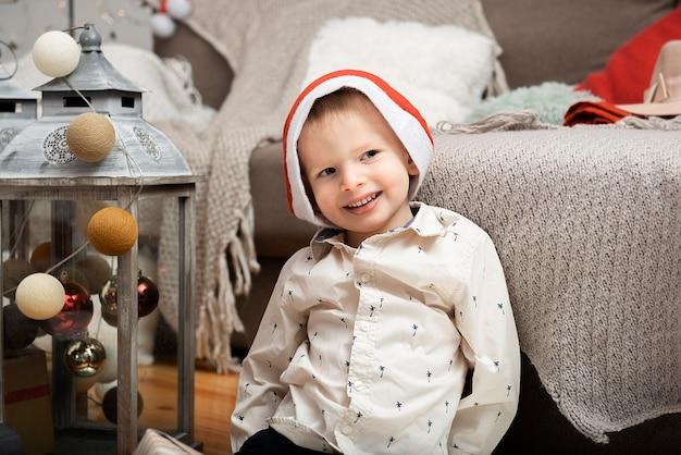 Ritratto di un grazioso piccolo ragazzo sorridente bambino che indossa un cappello di natale seduto tra le decorazioni per le vacanze a casa