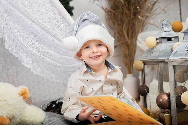 Ritratto di un piccolo bambino sorridente sveglio del ragazzo che porta un cappello di natale che si siede fra le decorazioni di festa