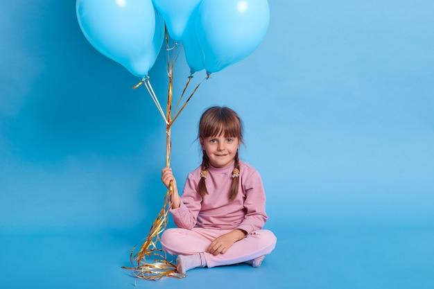 Ritratto di preschooler carino in posa contro il muro blu con palloncini