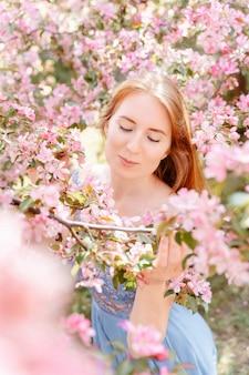 Ritratto di una ragazza carina dai capelli rossi vicino a un albero in fiore con fiori rosa nel parco fiorito di mele da giardino in primavera