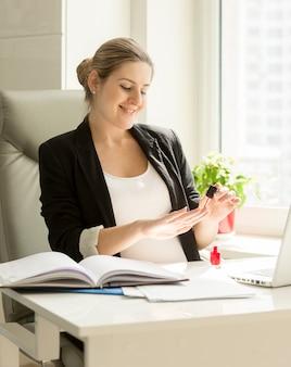 Ritratto di una segretaria carina che dipinge le unghie in ufficio
