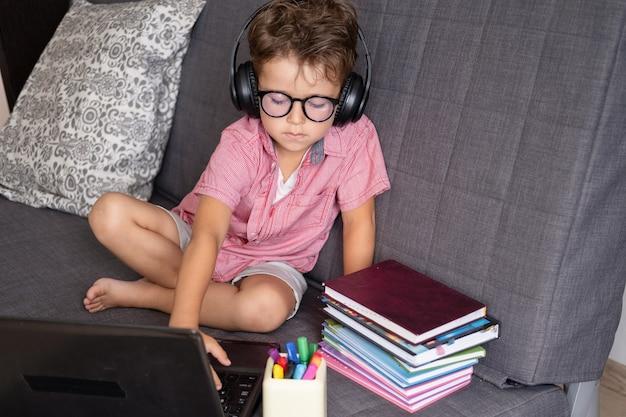 Ritratto di un simpatico ragazzo caucasico serio che utilizza laptop e cuffie mentre studia a casa, concetto di educazione remota. digitando. molti libri e blocco note sull'allenatore. quarantena. torna al concetto di scuola.