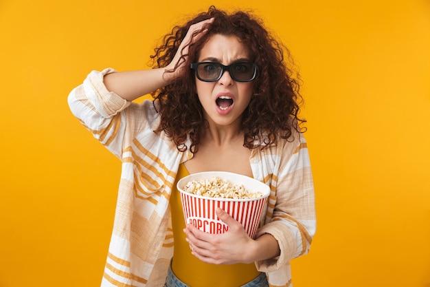 Ritratto di una bella giovane donna riccia scioccata carina in posa isolata sulla parete gialla con gli occhiali mangia popcorn guarda film.