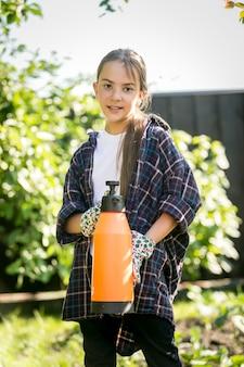 Ritratto di ragazza sorridente carina in posa in giardino con spray