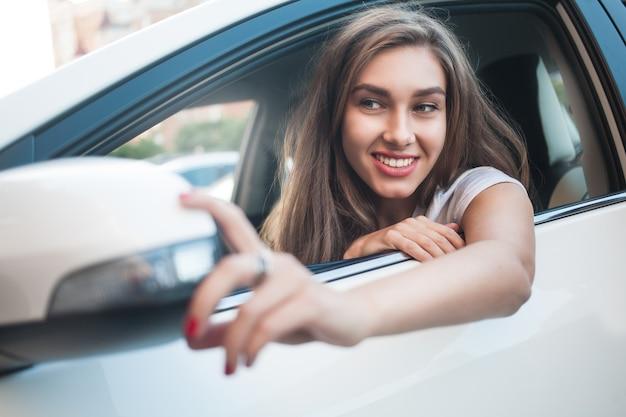 Il ritratto di una ragazza carina e sorridente si siede in macchina e guarda lo specchietto dell'auto