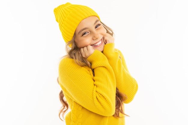 Ritratto di una ragazza adolescente carina sorridente in accoglienti abiti gialli e cappello su uno sfondo bianco