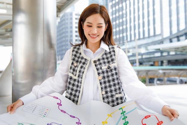Ritratto di una giovane donna asiatica adulta sorridente carina in abiti eleganti e casual alla moda in bianco e nero appoggiata al palo, con in mano una mappa della metropolitana di carta e guardando la telecamera con uno sfondo sfocato