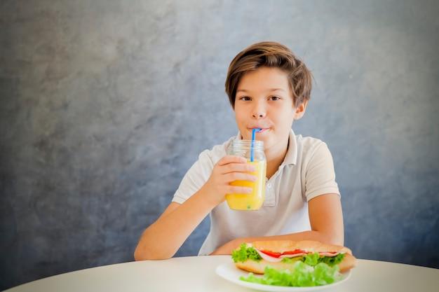 Ritratto del ragazzo teenager sveglio che mangia prima colazione a casa