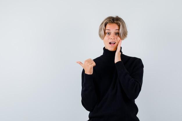 Ritratto di un ragazzo adolescente carino che punta a sinistra con il pollice, con la mano sulla guancia in un maglione a collo alto nero e che sembra una vista frontale meravigliata