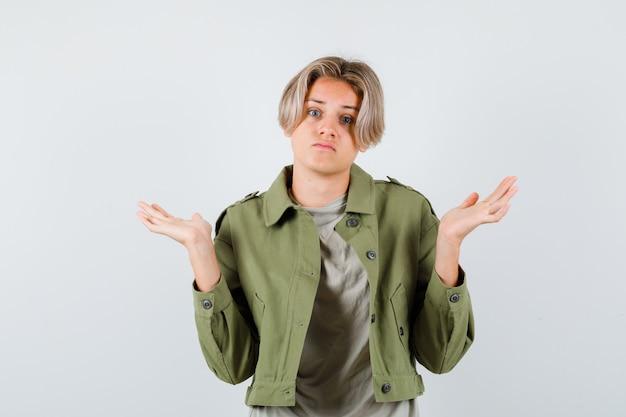 Ritratto di un ragazzo adolescente carino che mostra un gesto impotente in giacca verde e sembra confuso vista frontale