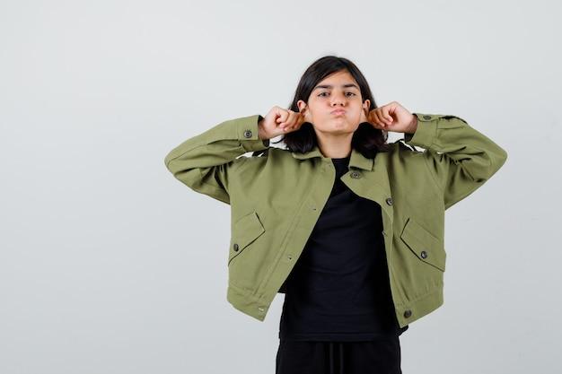 Ritratto di una ragazza adolescente carina che si tira giù i lobi delle orecchie, soffiando le guance in giacca verde militare e guardando la vista frontale dispiaciuta