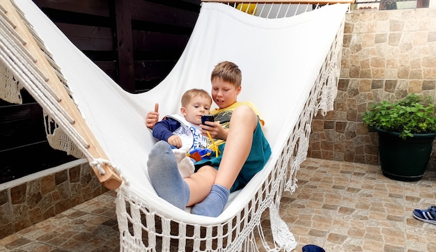 Ritratto di un bambino carino sdraiato con suo fratello maggiore su un'amaca e che usa smartphone
