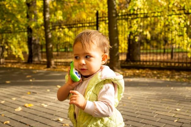 Ritratto di bambino carino che gioca parlando su un telefono giocattolo.