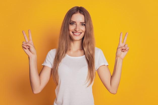 Ritratto di donna carina che mostra il segno v isolato su sfondo giallo