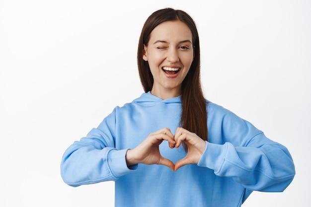 Ritratto di donna carina strizza l'occhio, esprime simpatia, come, mostrando il gesto del cuore e sorridendo civettuola, flirtando, in piedi contro il muro bianco in felpa con cappuccio blu