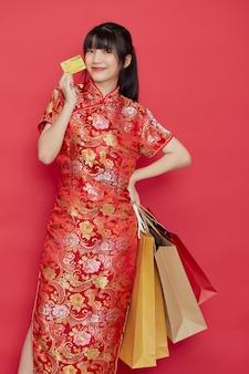 Ritratto carino giovane donna asiatica indossa un abito cinese con una borsa della spesa e una carta di credito per il capodanno cinese su un muro rosso
