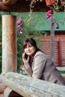 Ritratto di giovane donna di affari sveglia che chiama sul terrazzo all'aperto del telefono della casa di campagna. donna maniaca del lavoro in abiti casual domestici che lavorano in zone rurali. ispirazione creativa e attività di avvio. copia spazio