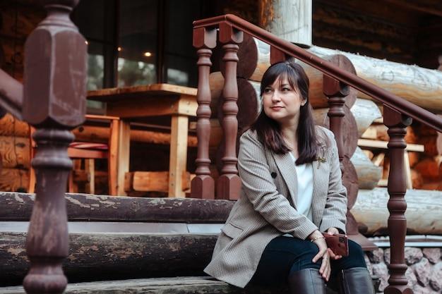 Ritratto di giovane donna d'affari carina nella terrazza all'aperto della casa in legno. bella donna in abiti casual domestici che camminano sul paese rurale. ispirazione creativa e attività di avvio. copia spazio