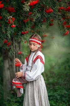 Ritratto di una ragazza carina in abiti folk vicino a un albero di rowan